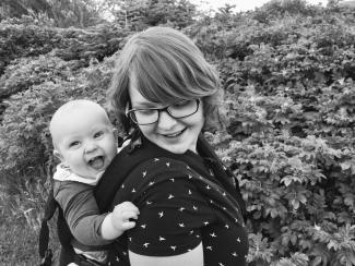 Mor med barn på ryggen i bæresele